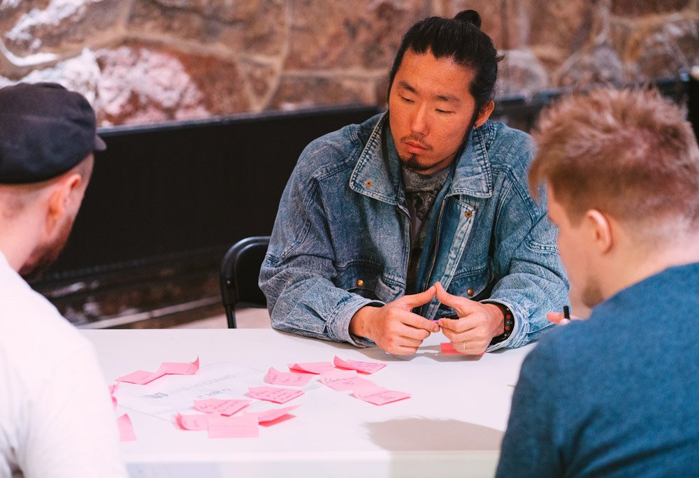 Tiimiläisiä suunnittelemassa pöydän ääressä post-it -lappujen keskellä